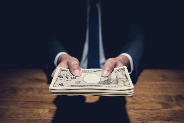Uomo d'affari che dà soldi, valuta di yen giapponesi, nella stanza scura