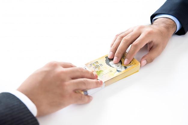 Uomo d'affari che dà soldi, valuta won sudcoreana, al suo partner