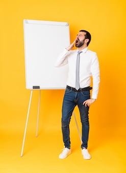 Uomo d'affari che dà una presentazione sul bordo bianco che sbadiglia e che copre la bocca spalancata con la mano