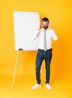 Uomo d'affari che dà una presentazione sul bordo bianco con mal di testa