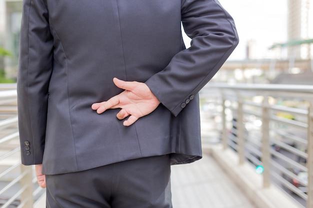 Uomo d'affari che dice bugie, tenere premuto il dito sulla schiena con sfondo moderno edificio