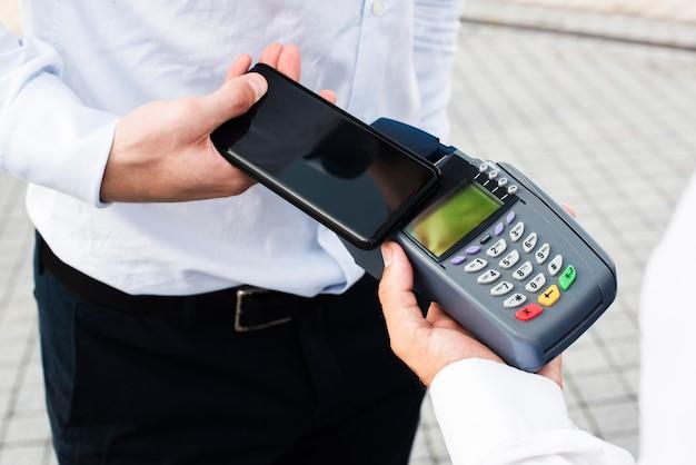 Uomo d'affari che effettua un pagamento per telefono