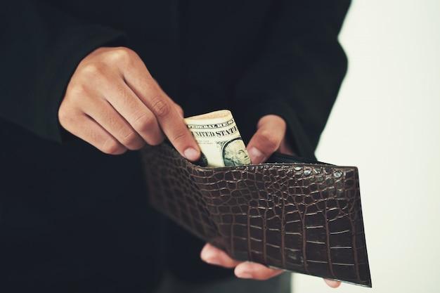 Uomo d'affari che elimina soldi dal portafoglio su bianco