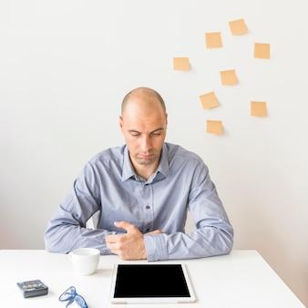 Uomo d'affari che esamina compressa digitale con lo schermo in bianco