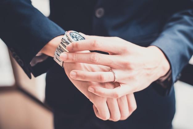 Uomo d'affari che esamina il suo orologio in ufficio. concetto per il business