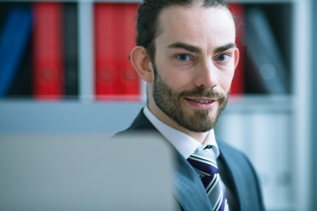 Uomo d'affari che fa capolino da dietro il monitor, esaminando la fotocamera