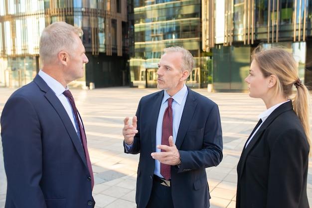 Uomo d'affari che fa domande ai suoi partner. uomini d'affari in piedi e parlare all'aperto, discutendo insieme il progetto. partenariato e concetto di comunicazione