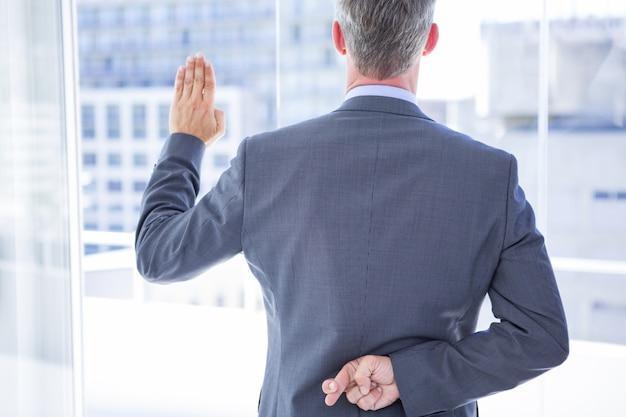 Uomo d'affari che fa un giuramento mentre attraversa le dita