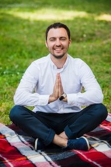Uomo d'affari che fa yoga su erba verde al parco con un computer portatile