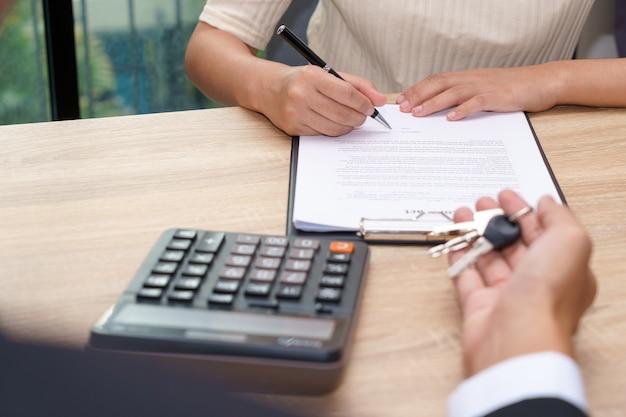 Uomo d'affari che fornisce il documento di accordo di prestito di firma del cliente e della chiave
