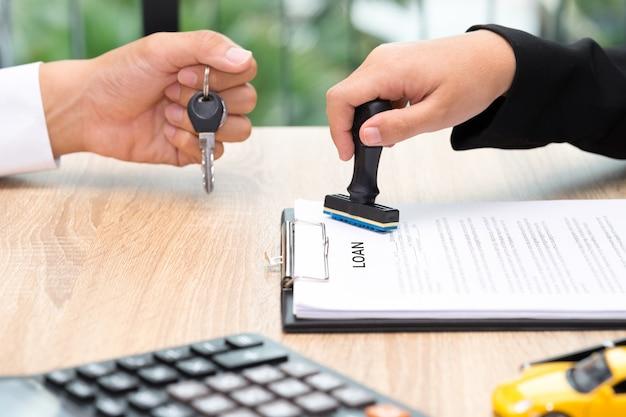 Uomo d'affari che fornisce la chiave dell'automobile mentre accordo di prestito che è approvato