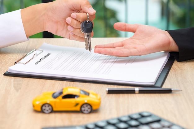 Uomo d'affari che fornisce la chiave dell'automobile sopra il documento di accordo di prestito con il giocattolo dell'automobile