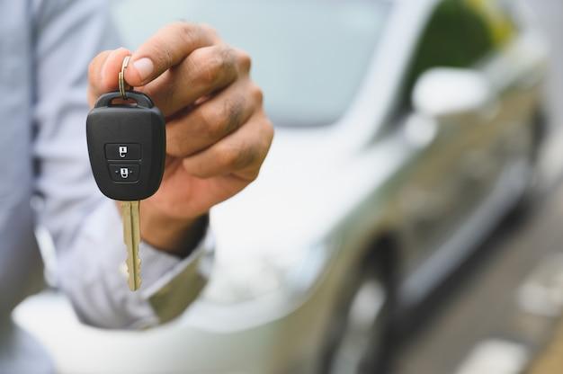 Uomo d'affari che fornisce una chiave dell'automobile. ottenere un nuovo concetto di auto.