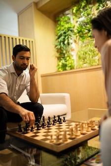 Uomo d'affari che gioca a scacchi con il collega di sesso femminile