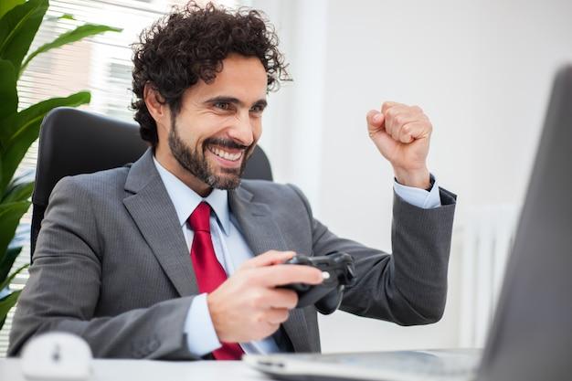 Uomo d'affari che gioca ai videogiochi nel suo ufficio invece di lavorare