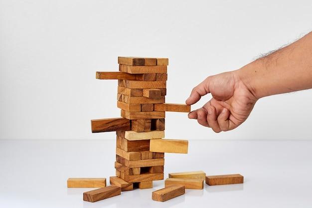 Uomo d'affari che gioca con il gioco di legno
