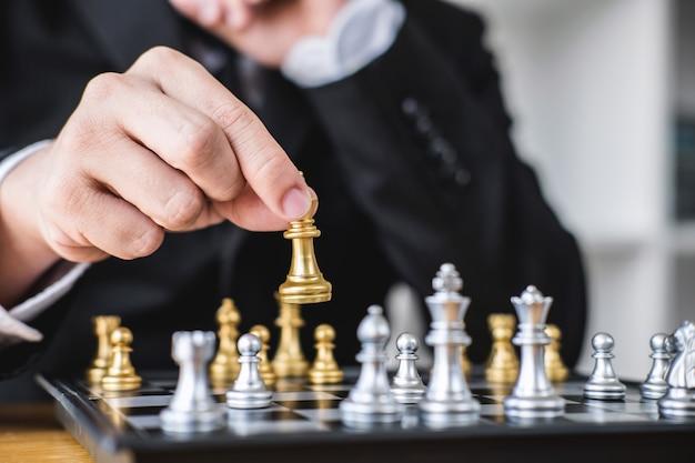 Uomo d'affari che gioca il gioco degli scacchi all'analisi di sviluppo nuovo piano di strategia