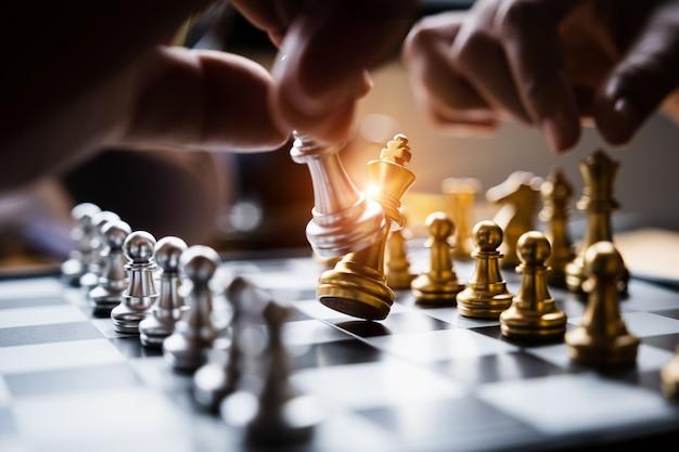 Uomo d'affari che gioca o che muove la figura di scacchi nel gioco di successo della concorrenza.