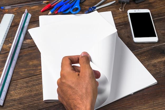 Uomo d'affari che gira carta bianca bianca con le cancellerie e lo smartphone sulla tavola di legno