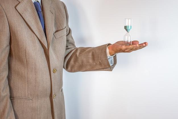 Uomo d'affari che giudica una clessidra isolata su bianco