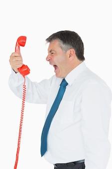 Uomo d'affari che grida direttamente nel telefono
