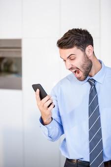 Uomo d'affari che grida mentre guardando in telefono cellulare