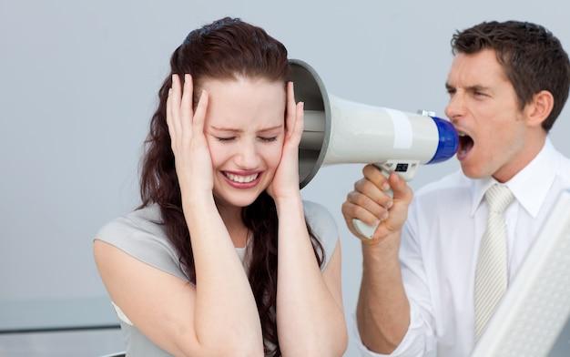 Uomo d'affari che grida tramite un megafono al suo collega