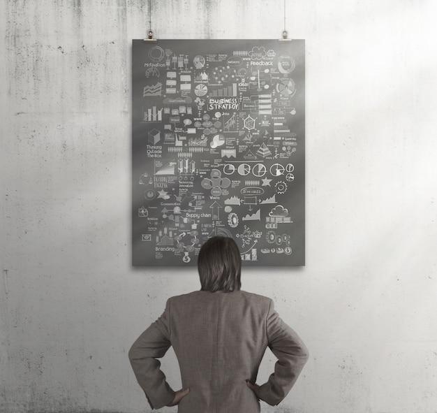 Uomo d'affari che guarda business plan sul manifesto con la parete della composizione