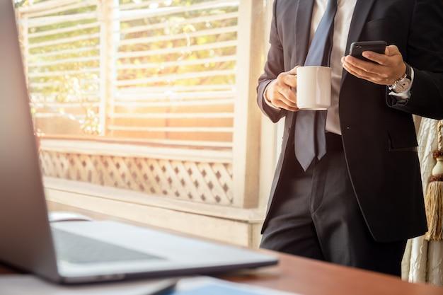 Uomo d'affari che ha pausa caffè e guardando cellulare.
