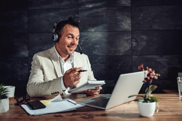 Uomo d'affari che ha riunione online nel suo ufficio