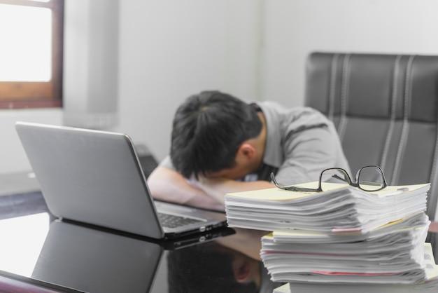 Uomo d'affari che ha sforzo con il computer portatile che lavora nell'ufficio