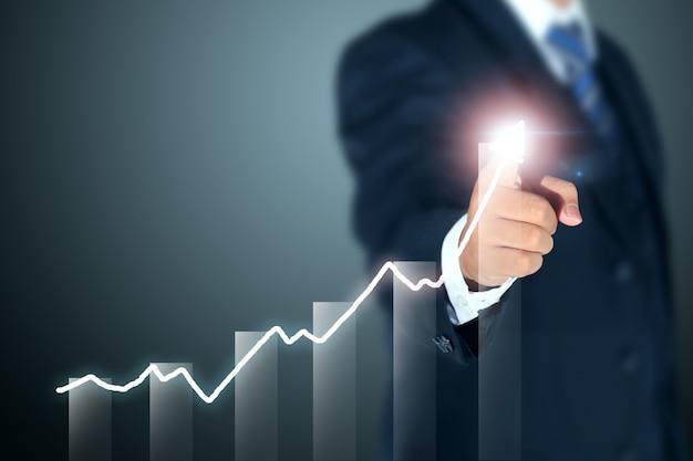 Uomo d'affari che indica il grafico del successo