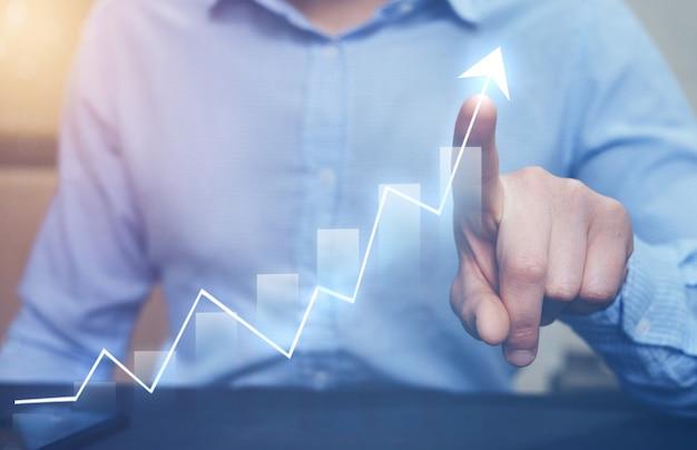 Uomo d'affari che indica il grafico della freccia che cresce corporativo