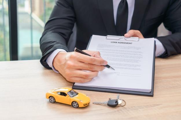 Uomo d'affari che indica il luogo dove dovrebbe firmare con il documento di accordo di prestito
