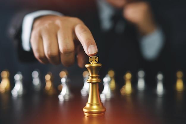 Uomo d'affari che indica il re di scacchi