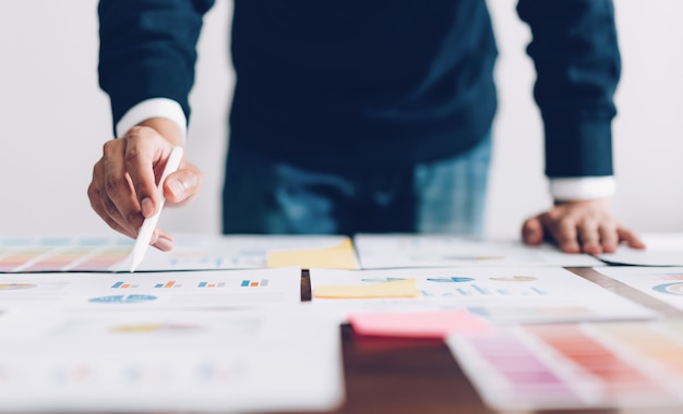 Uomo d'affari che indica le penne digitali e che lavora al tavolo e documenti finanziari in ufficio