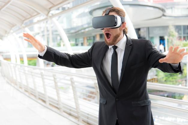 Uomo d'affari che indossa occhiali di realtà virtuale occhiali e godendo in questa attività