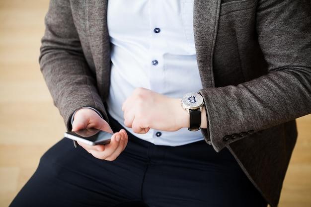 Uomo d'affari che investe nel bitcoin di valuta crypo, tiene nelle mani di un orologio di sabbia in attesa della crescita della valuta