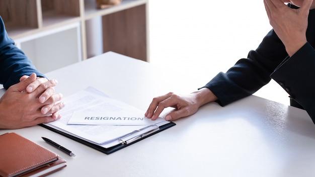 Uomo d'affari che invia la lettera di dimissioni al capo esecutivo del datore di lavoro sulla scrivania per dimettersi dal contratto