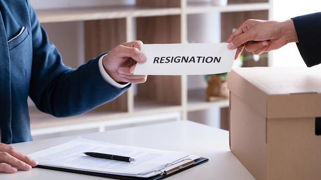 Uomo d'affari che invia la lettera di dimissioni al capo esecutivo del datore di lavoro sullo scrittorio per dimettersi dal contratto di licenziamento, dal collocamento e dal concetto di posti vacanti.
