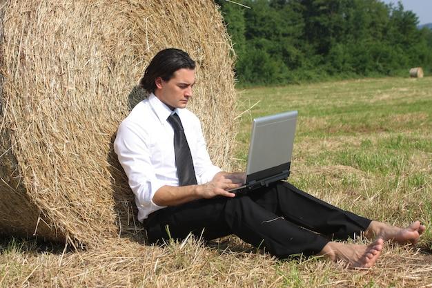 Uomo d'affari che lavora ad un computer portatile mentre appoggiandosi ad una balla