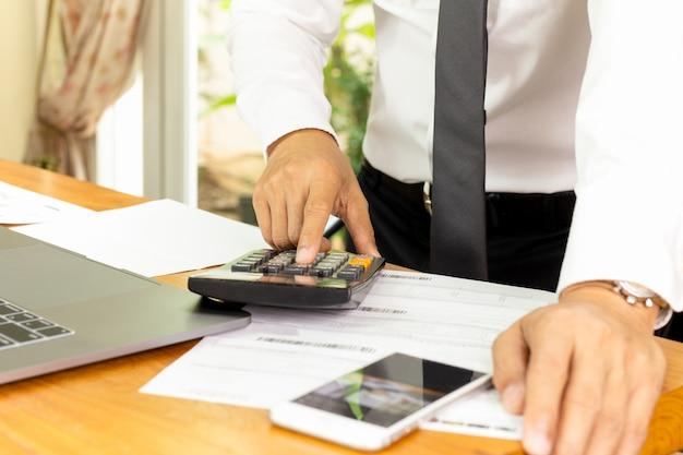 Uomo d'affari che lavora al calcolatore per calcolare il piano finanziario