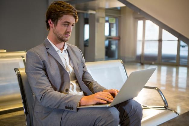 Uomo d'affari che lavora al suo computer portatile nell'area di attesa