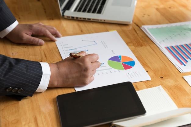 Uomo d'affari che lavora con documento documento scartoffie, tablet, computer portatile