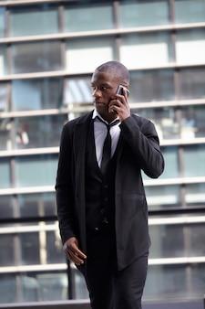 Uomo d'affari che lavora con il cellulare e il computer portatile