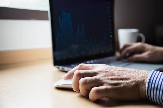 Uomo d'affari che lavora con il computer con la tazza di caffè nella camera d'albergo