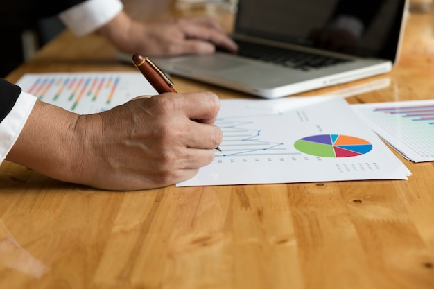 Uomo d'affari che lavora con il documento di scartoffie diagramma, computer portatile