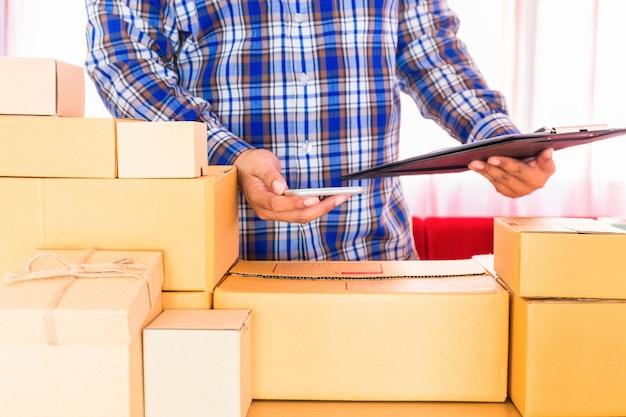 Uomo d'affari che lavora con il telefono cellulare e che imballa l'ufficio marrone della scatola dei pacchi a casa. il venditore delle mani prepara il prodotto pronto per la consegna al cliente. vendita online, e-commerce avvia il concetto di spedizione.