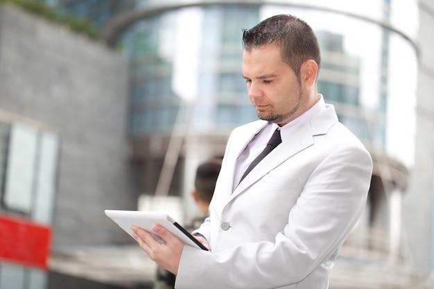 Uomo d'affari che lavora con la compressa digitale nell'ambiente urbano