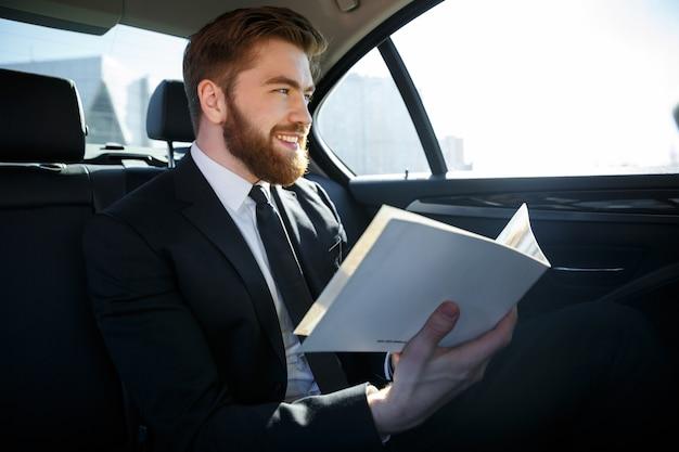 Uomo d'affari che lavora con le carte nel sedile posteriore